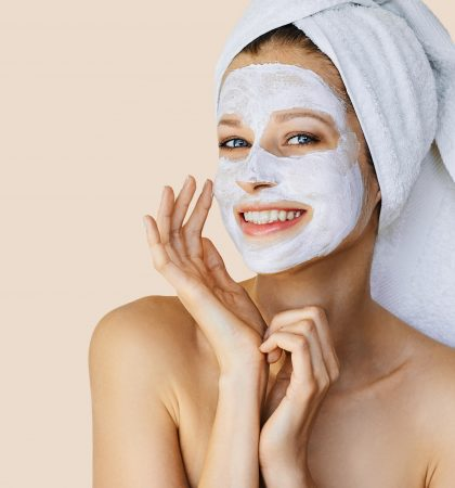 Beautiful young woman applying facial mask on her face. Skin care and treatment, spa, natural beauty and cosmetology concept.