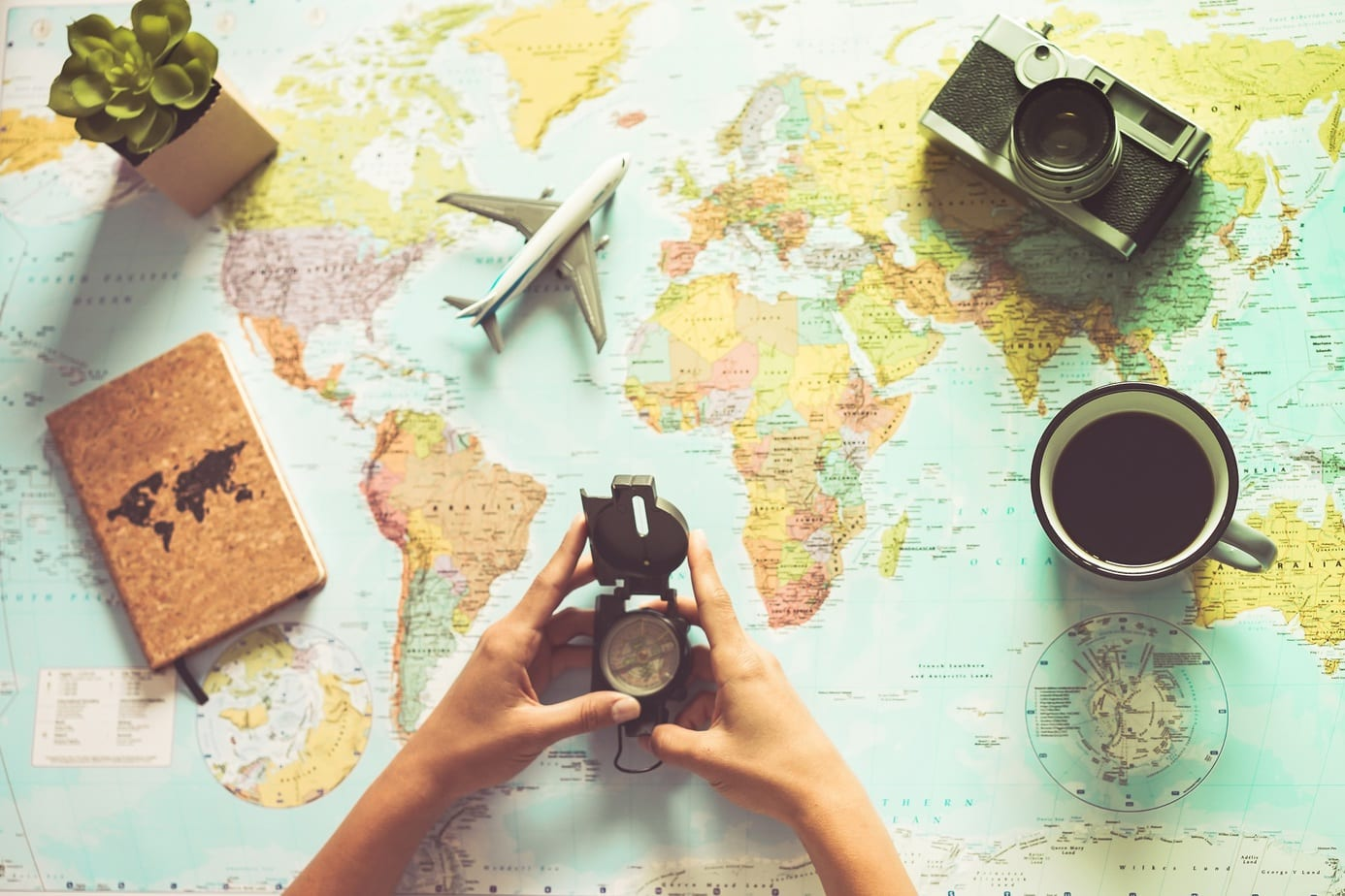 Young woman drinking coffee and planning world tour with vintage travel map – Backpacker girl looking for a new countries to explore – Journey trends, globetrotter and holiday concept – Focus on mug