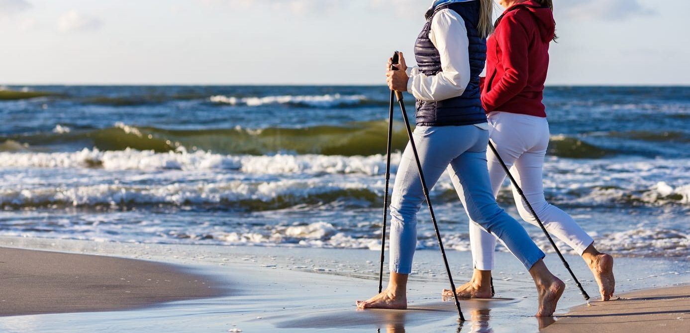 Nordic walking – two women working out on beach