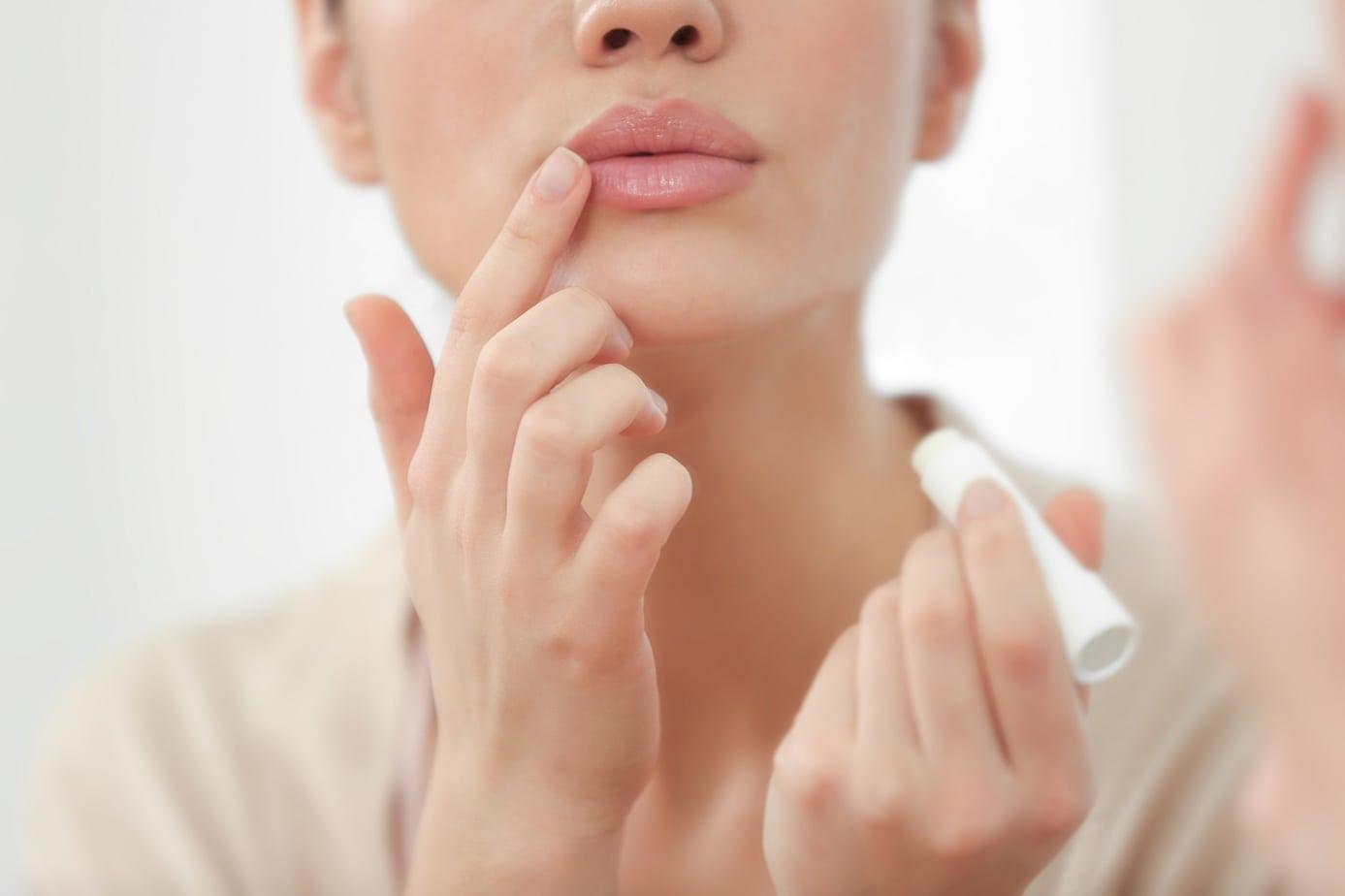 Woman applying hygienic lip balm near mirror